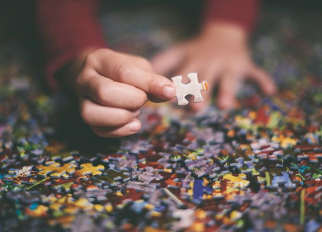 Hands and Jigsaw puzzle pieces on a table